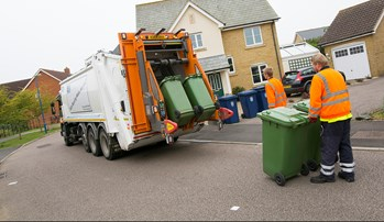 A bin collection lorry emptying two green bins