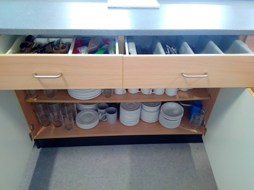 Cupboard in the kitchenette with a full set of cutlery and crockery