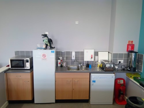 "This is an image of the kitchenette in the Cafe.  There is a microwave, dishwasher, toaster, hot water urn, fridge and model dragon holding a sign that says ""welcome to the wing""!"