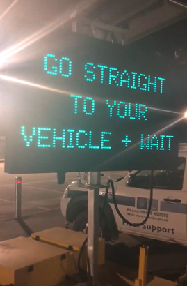 A sign that says go straight to your vehicle and wait