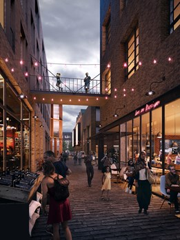 An artist impression of a street in the new Northstowe town centre. There are people walking between shops in the evening, twinkling red lights and a footbridge between two buildings