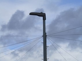 A streetlight. There is a cloudy sky in the background, along with power lines