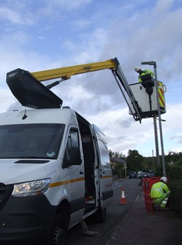 A white van with a cherry picker built into it. There are workers in high visibility clothing replacing a streetlight