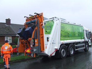 The Council's first electric bin lorry. It has a green paint job that contains trees, buildings with solar panels, the sun, wind turbines and other similar icons. There are two blue wheelie bins being emptied by a worker in a bright yellow jacket and trousters.